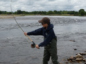 A youth fishing in the river Spey.